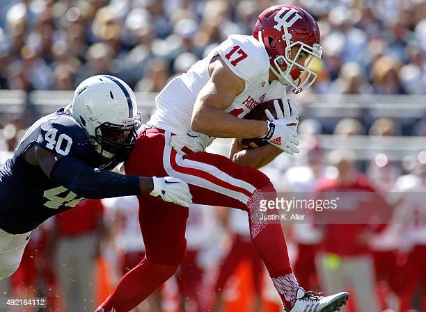 Isaac Griffith of the Indiana Hoosiers is tackled after making a catch by Jason Cabinda of the Penn State Nittany Lions in the first half during the...