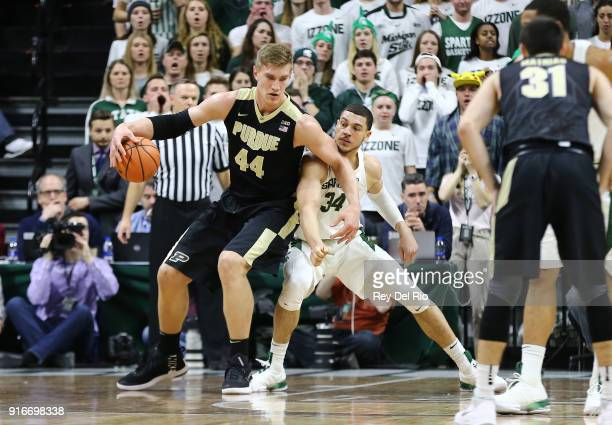 Isaac Haas of the Purdue Boilermakers posts up against Gavin Schilling of the Michigan State Spartans in the first half at Breslin Center on February...