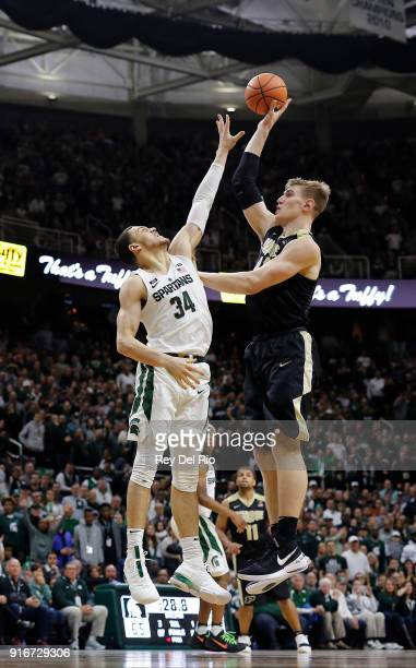 Isaac Haas of the Purdue Boilermakers shoots over Gavin Schilling of the Michigan State Spartans in the second half at Breslin Center on February 10...