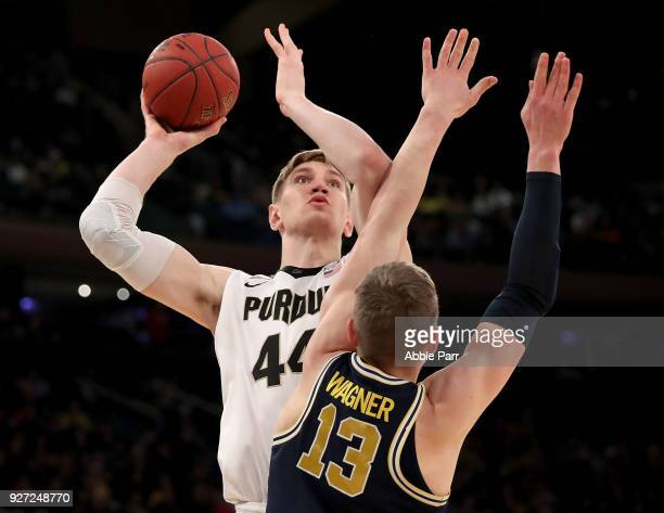 Isaac Haas of the Purdue Boilermakers takes a shot against Moritz Wagner of the Michigan Wolverines in the second half during the championship game...