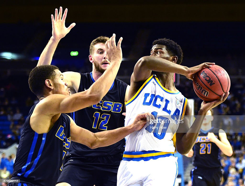 Isaac Hamilton #10 of the UCLA Bruins drives to the basket as he is defended by Eric Childress #1 and Alex Hart #12 of the UC Santa Barbara Gauchos during a 102-62 win over the UC Santa Barbara Gauchos at Pauley Pavilion on December 14, 2016 in Los Angeles, California.