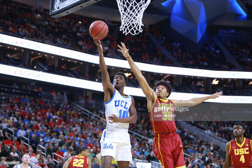 Isaac Hamilton #10 of the UCLA Bruins handles the ball against Elijah Stewart #30 of the USC Trojans during a quarterfinal game of the Pac-12 Basketball Tournament at T-Mobile Arena on March 9, 2017 in Las Vegas, Nevada. UCLA won 76-74.