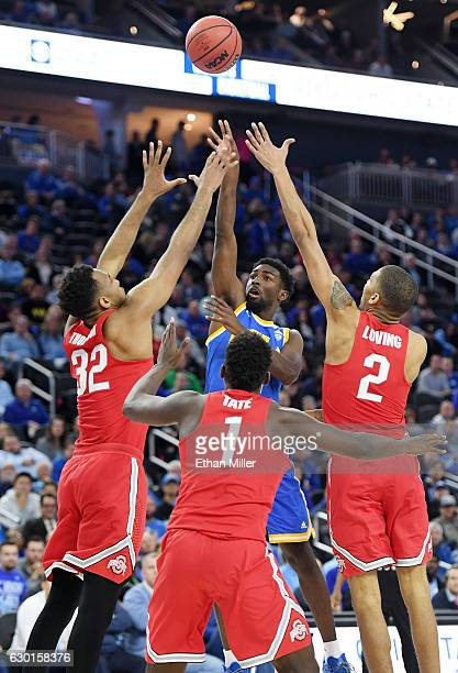 Isaac Hamilton of the UCLA Bruins shoots against Trevor Thompson Jae'Sean Tate and Marc Loving of the Ohio State Buckeyes during the CBS Sports...