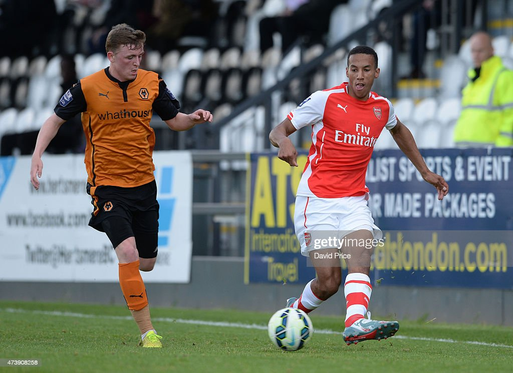 Isaac Hayden of Arsenal passes the ball awy from Ryan Rainey of Wolves during the match between Arsenal U21s and Wolverhampton Wanderers U21s at Meadow Park on May 18, 2015 in Borehamwood, England.