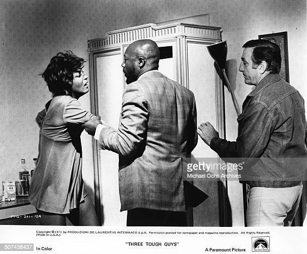 Isaac Hayes roughly questions Paula Kelly as Lino Ventura stand as backup in a scene from the Paramount Pictures movie Three Tough Guys circa 1974