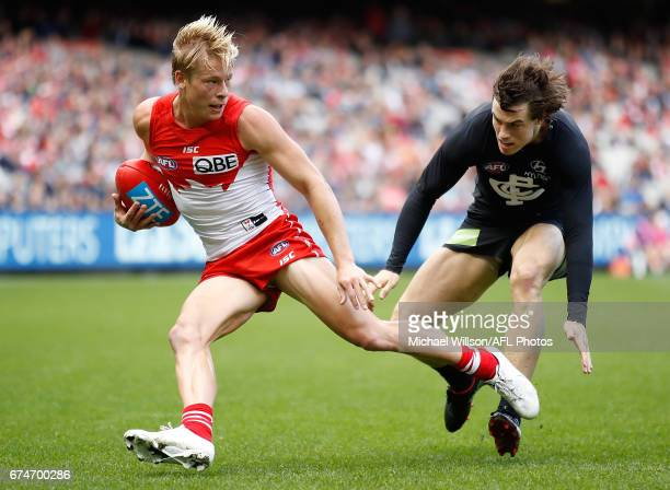 Isaac Heeney of the Swans evades Lachie Plowman of the Blues during the 2017 AFL round 06 match between the Carlton Blues and the Sydney Swans at the...
