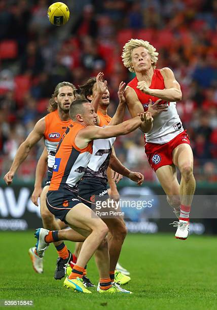 Isaac Heeney of the Swans gets a handball away despite pressure from Tom Scully of the Giants during the round 12 AFL match between the Greater...