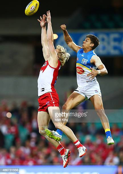 Isaac Heeney of the Swans is challenged by Sean Lemmens of the Suns during the round 23 AFL match between the Sydney Swans and the Gold Coast Suns at...