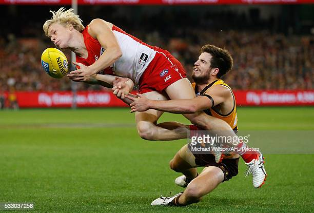 Isaac Heeney of the Swans is tackled by Ben Stratton of the Hawks during the 2016 AFL Round 09 match between the Hawthorn Hawks and the Sydney Swans...