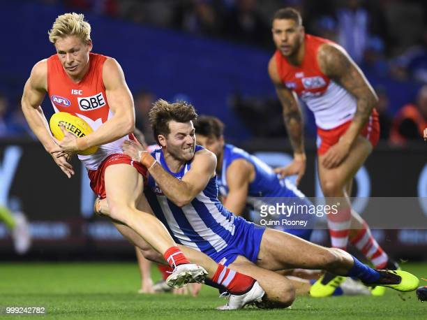 Isaac Heeney of the Swans is tackled by Luke McDonald of the Kangaroos during the round 17 AFL match between the North Melbourne Kangaroos and the...