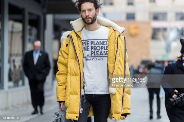 Isaac HindinMiller wearing a yellow parka white tshirt outside Creatures of the Wind on February 11 2017 in New York City