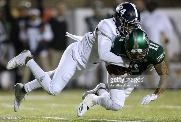 Isaac Holder of the Eastern Michigan Eagles is tackled by Sean Freeman of the Georgia Southern Eagles during the first half of the Raycom Media...