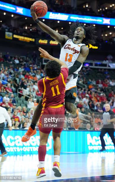 Isaac Likekele of the Oklahoma State Cowboys lays the ball up against Prentiss Nixon of the Iowa State Cyclones in the first half during the first...