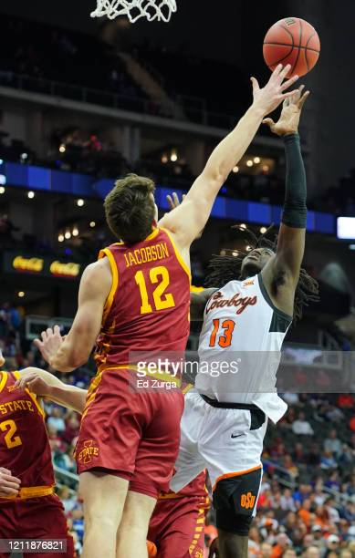 Isaac Likekele of the Oklahoma State Cowboys lays the ball up against Michael Jacobson of the Iowa State Cyclones in the first half during the first...