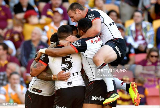 Isaac Luke of the Warriors is congratulated by team mates after scoring a try during the round 18 NRL match between the Brisbane Broncos and the New...