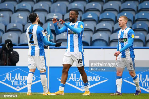 Isaac Mbenza of Huddersfield Town celebrates with team mates Pipa and Lewis O'Brien after scoring their side's second goal during the Sky Bet...