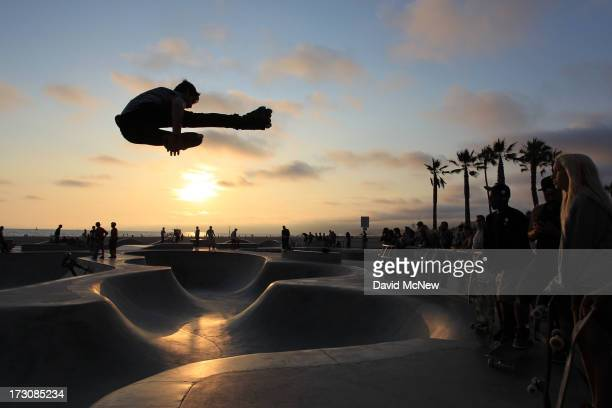 Isaac Mercado makes a jump on rollerblades at sunset on Independence Day weekend at Venice Beach on July 5 2013 in Venice California An estimated 16...