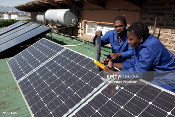 Isaac Molelelu and Thabisa Siyokwana installs and checks solar panels on April 20 2012 in Cape Town South Africa They study at a solar installation...
