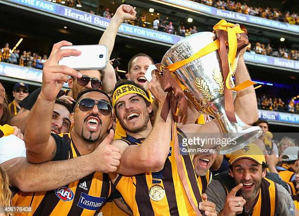 Isaac Smith of the Hawks celebrates with fans and the Premeirship Cup during the 2014 AFL Grand Final match between the Sydney Swans and the Hawthorn...