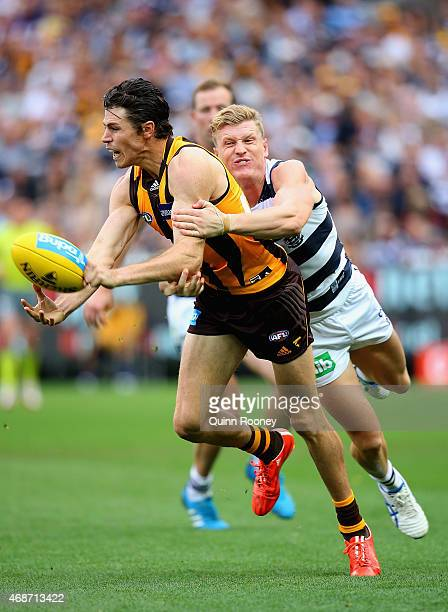 Isaac Smith of the Hawks handballs whilst being tackled by Josh Caddy of the Cats during the round one AFL match between the Hawthorn Hawks and the...