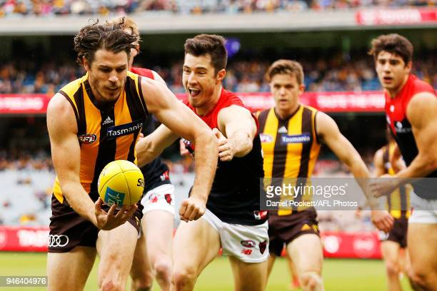 Isaac Smith of the Hawks handpasses the ball whilst being tackled by Alex NealBullen of the Demons during the round four AFL match between the...
