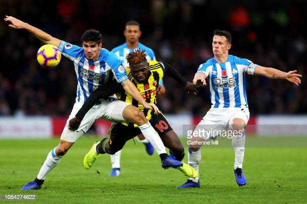 Isaac Success of Watford is challenged by Christopher Schindler of Huddersfield Town and Jonathan Hogg of Huddersfield Town during the Premier League...