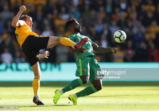 Isaac Success of Watford is challenged by Ryan Bennett of Wolverhampton Wanderers during the Premier League match between Wolverhampton Wanderers and...
