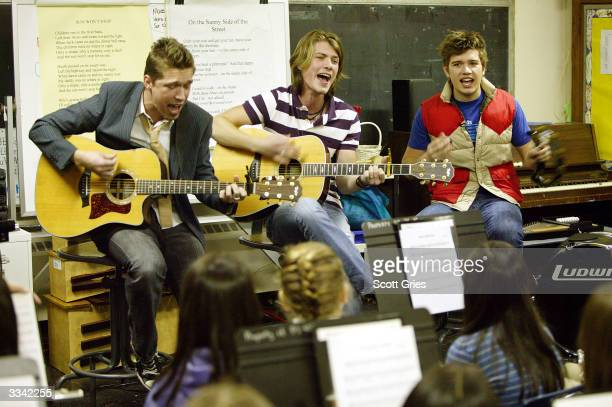Isaac Taylor and Zac of the rock band Hanson perform at PS 40 as part of the VH1 Save The Music Master Class April 12 2004 in New York City