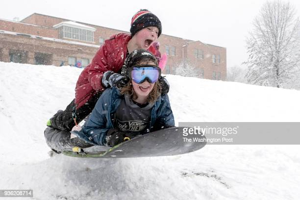 Isaac Wright bottom and Nathan Schneck fly off a mound while sledding in Takoma Park MD on March 21 2018