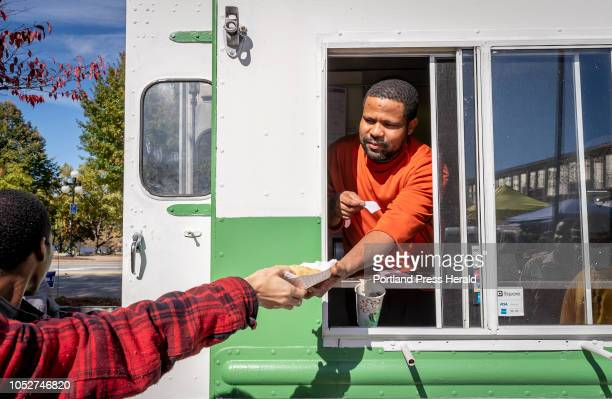 Isaack Gawo hands an order of a sambusa to a customer as he works on the Isuken Coop food truck Sunday Oct 14 2018 at the Lewiston Farmers' Market in...