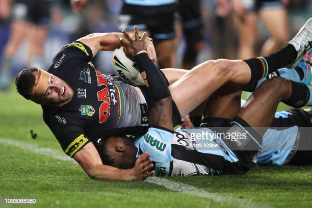 Isaah Yeo of the Panthers is tackled by James Segeyaro of the Sharks as he scores a try during the NRL Semi Final match between the Cronulla Sharks...