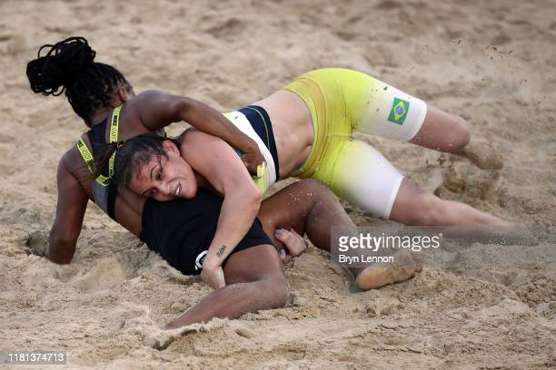 Isabel Cristina Rodrigues of Portugal fights Camila Tristao Fama in the Women's 60KG weight at the Beach Wrestling competition at Katara Beach during...