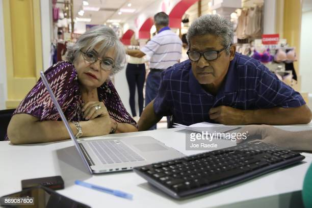 Isabel Diaz Tinoco and Jose Luis Tinoco look at a computer as Otto Hernandez, an insurance agent from Sunshine Life and Health Advisors, shows them...