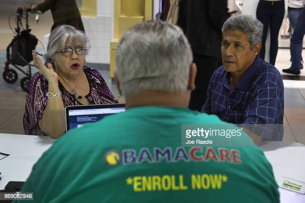Isabel Diaz Tinoco and Jose Luis Tinoco speak with Otto Hernandez, an insurance agent from Sunshine Life and Health Advisors, as they shop for...