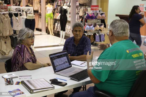 Isabel Diaz Tinoco and Jose Luis Tinoco speak with Otto Hernandez an insurance agent from Sunshine Life and Health Advisors as they shop for...