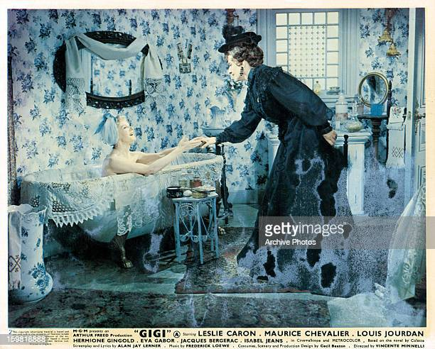 Isabel Jeans reaches out to Hermione Gingold from the bathtub in a scene from the film 'Gigi' 1958