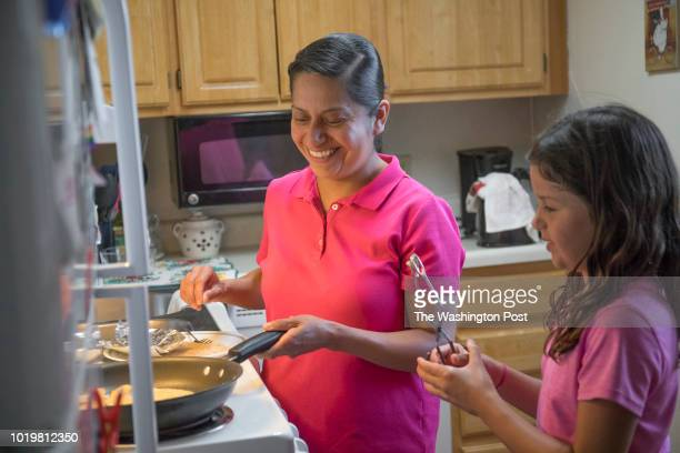 Isabel Moctezuma cooks dinner with her eightyearold daughter Mia in Ames Iowa on July 18 2018