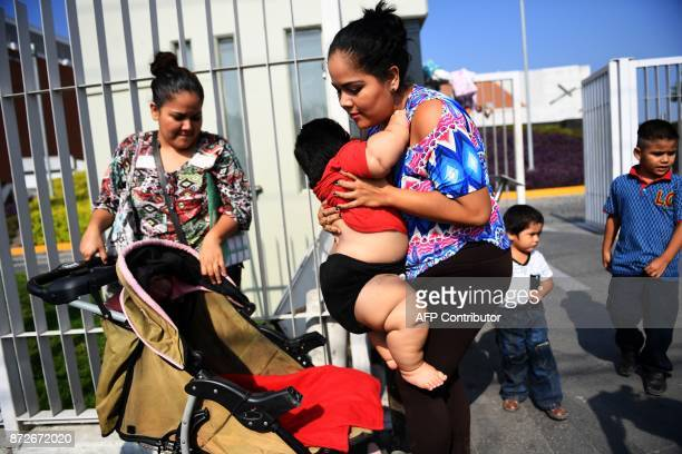 Isabel Pantoja holds her tenmonthold baby Luis Gonzales as they arrive at a clinic in Colima city for Luis' medical checkup in Mexico on November 9...