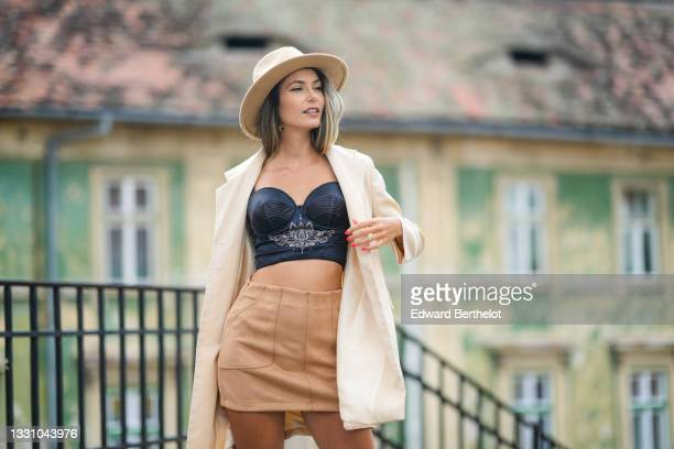 Isabela Francesca wears a beige felt / wool hat, a gold pendant earring, a black shiny satin with white embroidered pattern shoulder-off corset / bra...