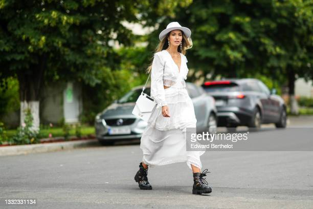 Isabela Francesca wears a white felt / wool hat, white pearls pendant earrings, a white V-neck / long sleeves / cut-out / embroidered lace ruffled...