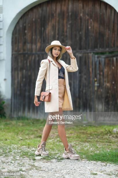 Isabela Francesca wears Isabela Francesca wears a beige felt / wool hat, a gold pendant earring, a black shiny satin with white embroidered pattern...