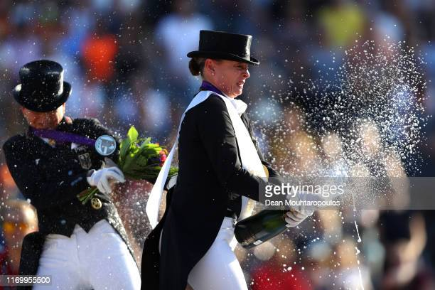 Isabell Werth of Germany riding Bella Rose celebrates winning the gold medal with champagne on Day 6 in the Grand Prix Freestyle, Longines FEI...