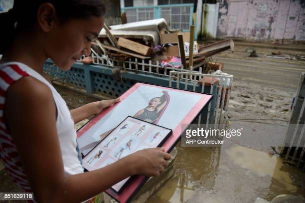 Isabella age 10 rescues her photos from her flooded house after the rains related to the passage of Hurricane Maria in Toa Baja Puerto Rico on...