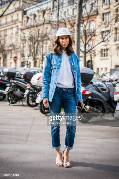 Isabella Charlotta Poppius poses with a white Supreme cap embroidered denim jacket by Etre Cecile jeans by Acne Studios bag by Dior and silver shoes...