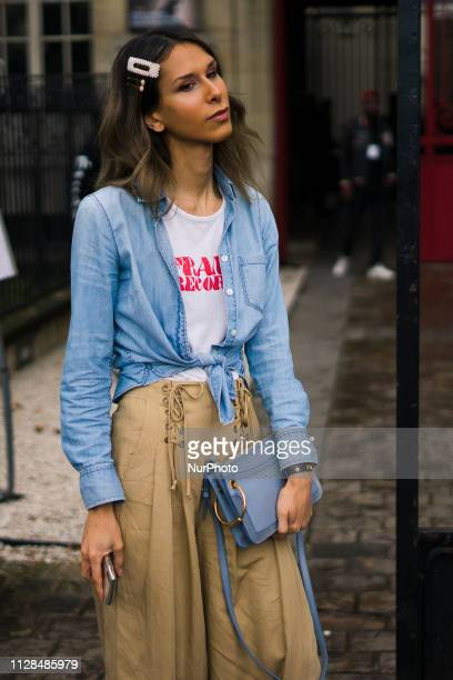 Isabella Charlotta Poppius wearing a denim shirt and white logo tshirt by Frame a pearl hair clip and jewelled hair pins beige highwaisted flared...