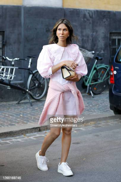 Isabella Charlotta Poppius, wearing a rose colored dress by Ganni, a rose colored sweater by Gestuz, white sneakers by Adidas and a small beige bag...