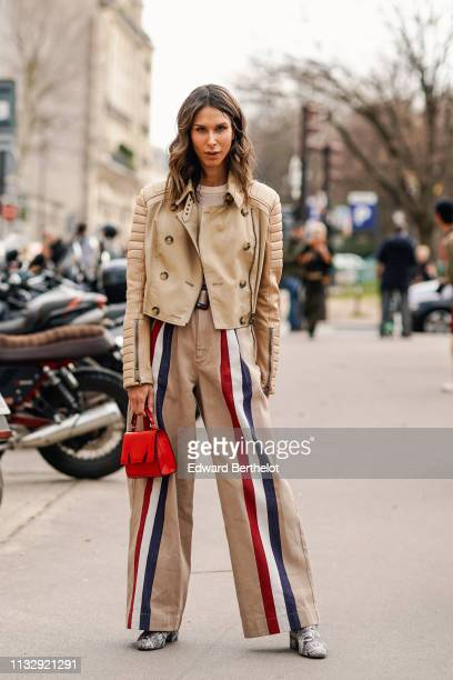 Isabella Charlotta Poppius wears a beige leather doublebreasted biker jacket by Burberry a red mini handbag by MSGM beige high waisted wide leg pants...