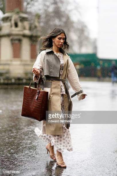 Isabella Charlotta Poppius wears a brown leather crocodile pattern bag a white gray and beige trench coat from Eudon Choi, a white dress with printed...
