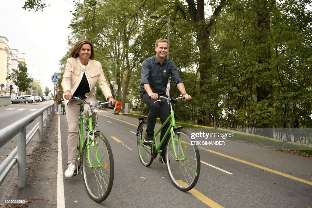 Isabella Lovin and Gustav Fridolin, spokespersons for the Green Party, ride bikes to join the Peoples Climate March in Stockholm, Sweden September 8, 2018. - Sweden holds legislative elections on Sunday, September 9, 2018, with polls predicting a parliamentary deadlock as neither Prime Minister Stefan Lofven's left-wing bloc nor the opposition centre-right are seen winning a majority, while the far-right makes gains. (Photo by Erik SIMANDER / TT News Agency / AFP) / Sweden OUT