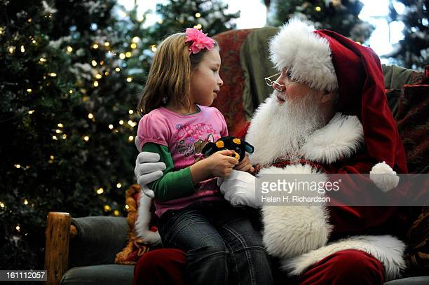 Isabella Martinez of Erie enjoys sitting on Santa's lap Santa Claus was a popular attraction at Flatirons Mall in Broomfield with only two days left...